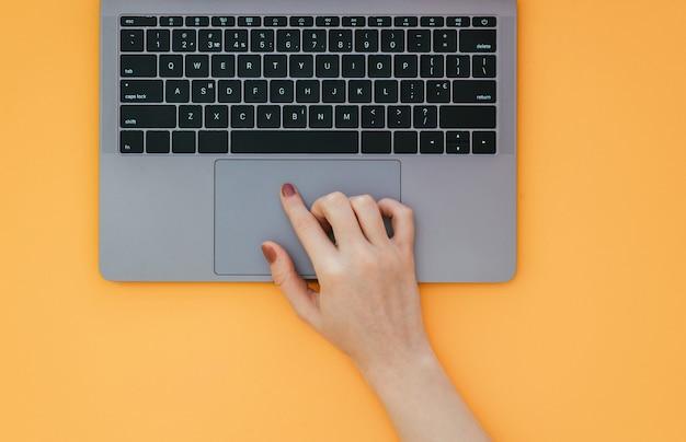 Feminino mão usa um touchpad em um laptop em uma superfície laranja