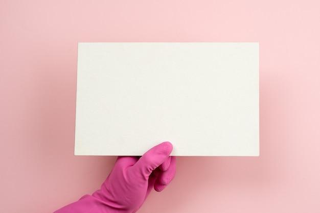 Feminino mão usando uma luva de látex rosa segurando uma maquete vazia branca em branco