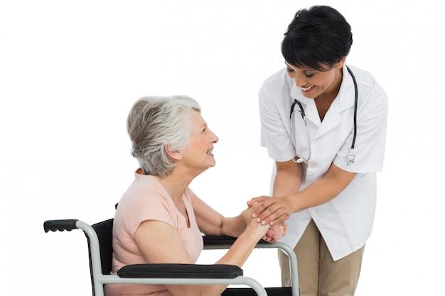 Feminino médico falando com um paciente sênior em cadeira de rodas