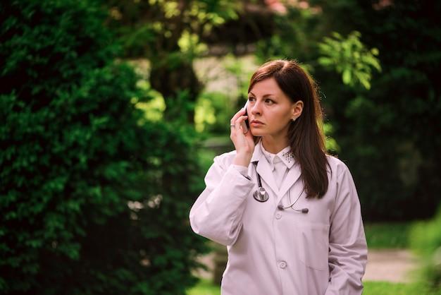 Feminino médico falando no celular sobre uma árvores verdes