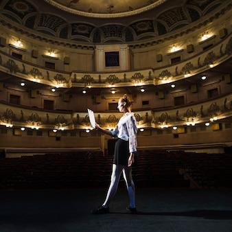 Feminino mime lendo manuscrito no auditório vazio