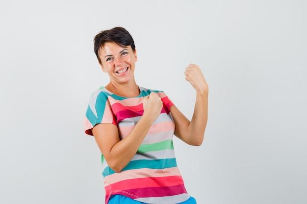 Feminino mostrando gesto de vencedor em t-shirt listrada e parecendo feliz. vista frontal.