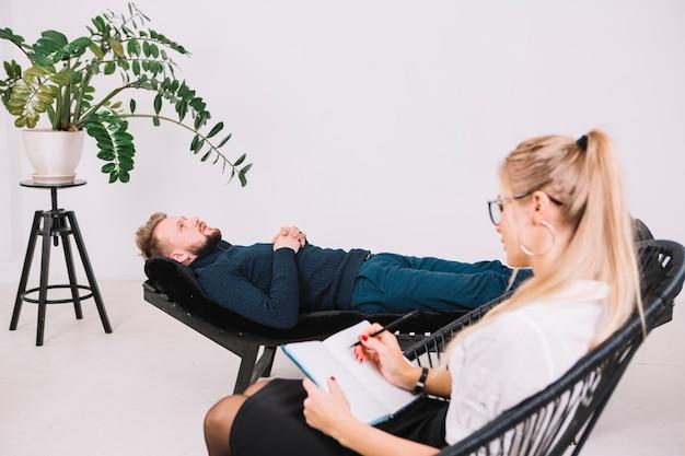 Feminino psicólogo escrevendo notas no diário enquanto paciente deitado no sofá na clínica