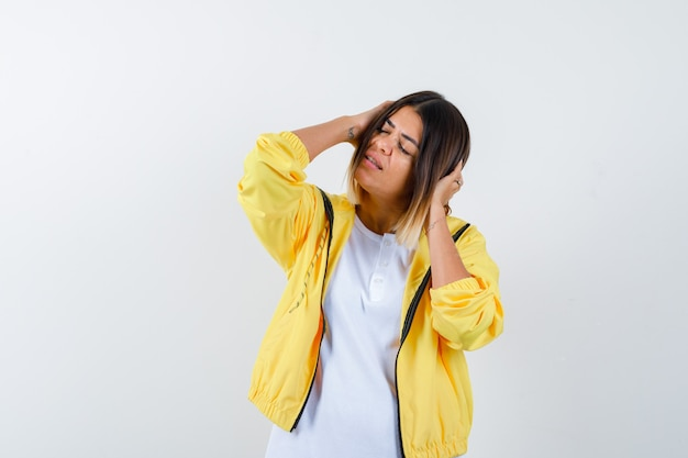 Feminino, segurando a cabeça nas mãos em t-shirt, jaqueta e parecendo relaxado, vista frontal.