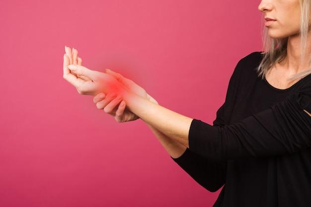 Feminino segurando a mão no local da dor no pulso. foto do conceito com pele color enhanced com ponto de leitura indicando a localização da dor.
