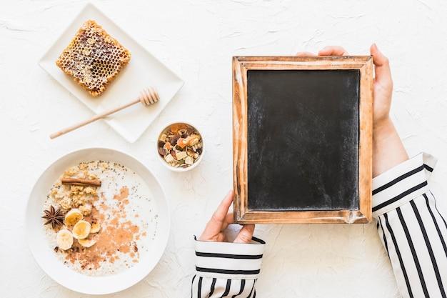 Feminino segurando o quadro-negro com farinha de aveia; dryfruits e favo de mel no pano de fundo branco