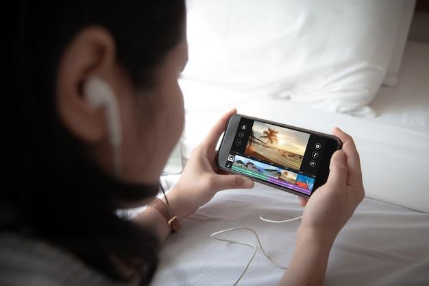 Feminino, segurando o telefone móvel e usando fone de ouvido