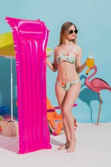 Feminino segurando rosa colchão e bebida de laranja