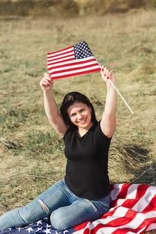 Feminino sentado e levantando a bandeira americana