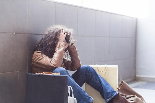 Feminino sentado no chão com sacos de compras