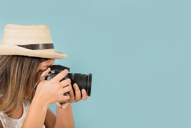 Feminino turista tira uma foto com câmera profissional contra o pano de fundo azul