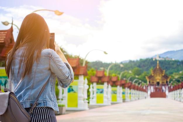 Feminino turista tirando foto do templo budista em chiangmai, tailândia com móvel inteligente