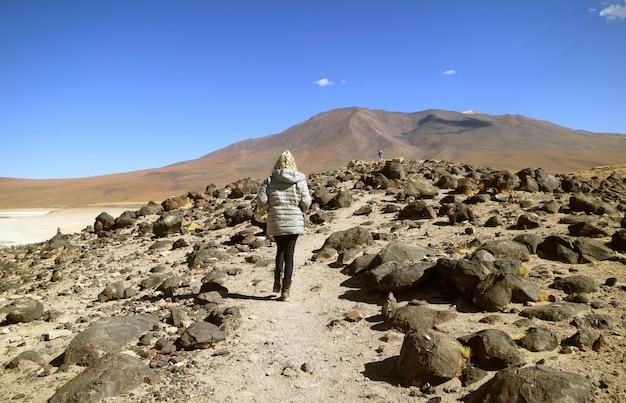 Feminino viajante andando na encosta da margem do lago laguna verde, potosi, bolívia