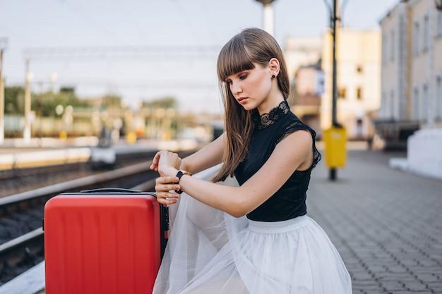 Feminino viajante com mala vermelha esperando trem na estação ferroviária