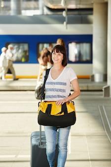 Feminino viajante com mochila e mala na estação de trem