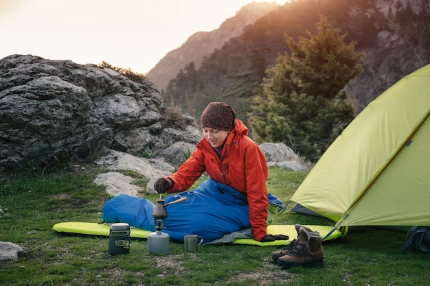 Feminino viajante cozinhando nas montanhas