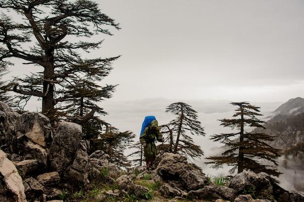 Feminino viajante em capa de chuva caminhadas no topo