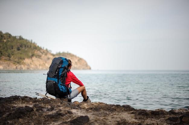 Feminino viajante em jacketsits perto do mar