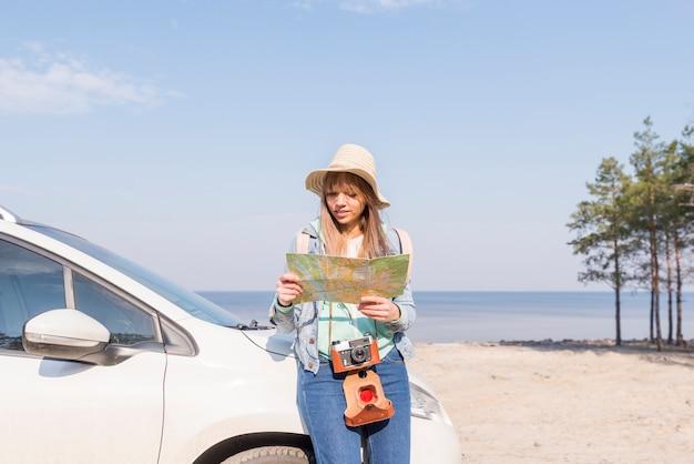 Feminino viajante inclinando-se perto do carro procurando localização no mapa