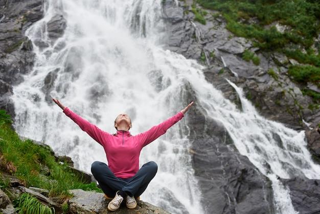 Feminino viajante sentado na cachoeira balea na romênia