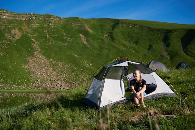 Feminino viajante sentado na tenda, aproveitando a manhã de verão perto do lago nas montanhas