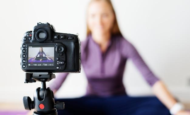 Feminino vlogger gravando esportes relacionados com transmissão em casa