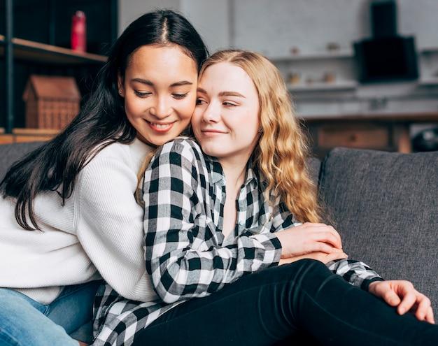 Femininos amigos multiétnicas abraçando
