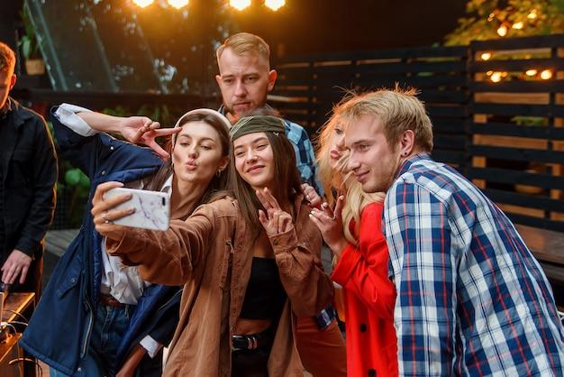 Femininos e masculinos amigos comemorando a festa ao ar livre e fazendo selfies foto no smartphone. jovens caucasianos se divertindo e curtindo o fim de semana na festa.