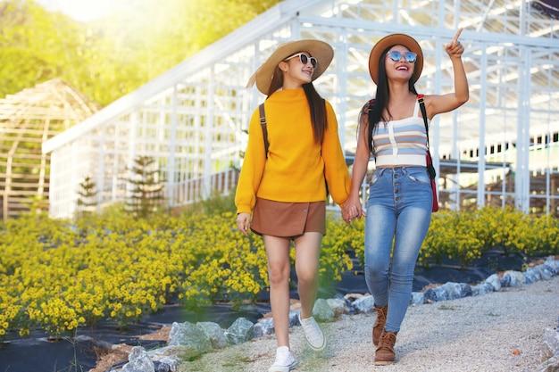 Femininos turistas caminham segurando os braços