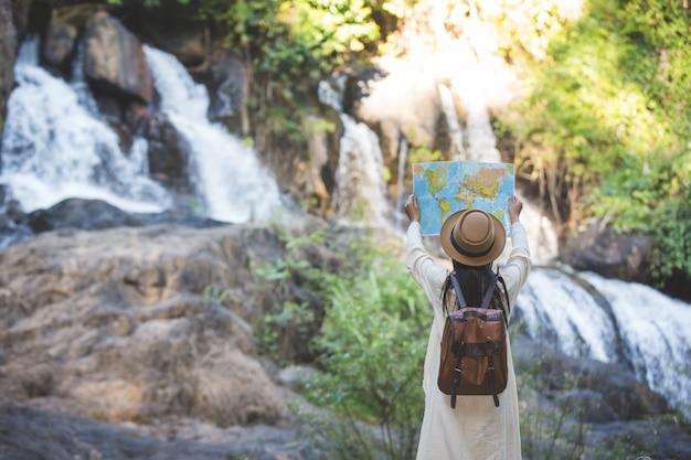 Femininos turistas na mão têm um mapa de viagem feliz.