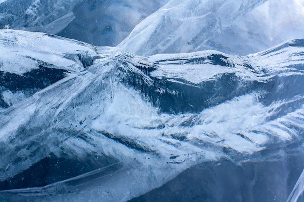 Fendas interessantes no gelo espesso do lago são semelhantes a cadeias de montanhas. gelo transparente azul espesso. horizontal.