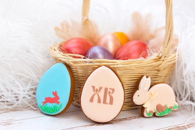 Feriado da páscoa. ovos coloridos em uma cesta. ovos de páscoa de gengibre e coelho. sobre um fundo claro. tradução de letras russas: cr (cristo ressuscitou)
