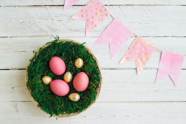 Feriado da páscoa. ovos de páscoa de cor rosa e ouro mentem em uma cesta