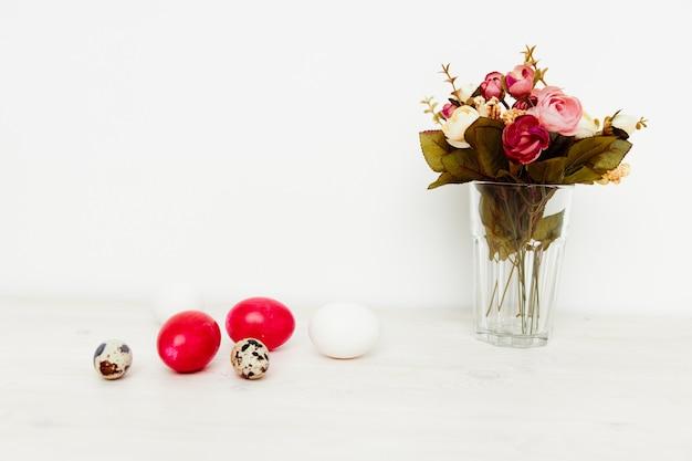 Feriado da ressurreição de cristo, ovos de páscoa vermelhos e um buquê de flores em um vaso.