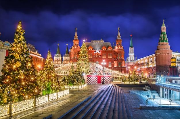 Feriado de ano novo com árvores decoradas na praça manezhnaya e o museu histórico à noite
