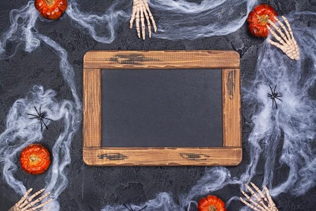 Feriado de halloween com mãos de esqueletos, abóboras, aranhas e teia de aranha no preto