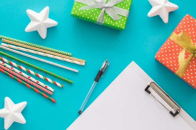 Feriado de natal e ano novo para fazer a lista com o bloco de notas, caneta, caixas de presente, tubos de coquetel, estrelas