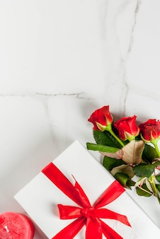 Feriado, dia dos namorados. buquê de rosas vermelhas, amarre com uma fita vermelha, com caixa de presente embrulhada. na mesa de mármore branca, vista superior copyspace