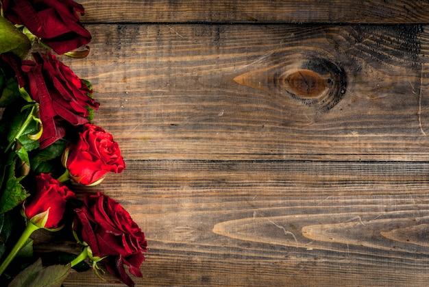 Feriado, dia dos namorados. buquê de rosas vermelhas, amarre com uma fita vermelha. em uma mesa de madeira, vista superior copyspace