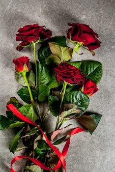 Feriado, dia dos namorados. buquê de rosas vermelhas, amarre com uma fita vermelha. em uma mesa de pedra cinza, vista superior copyspace