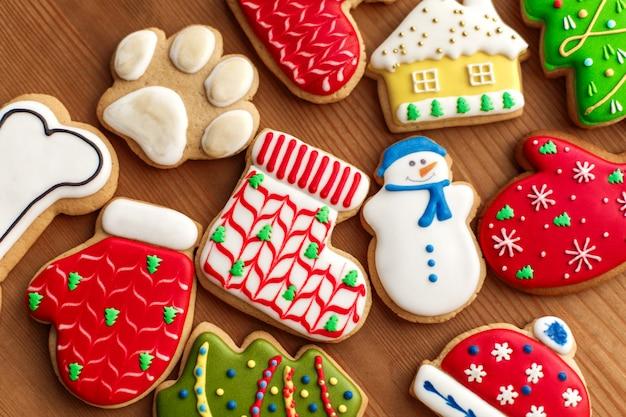 Feriado do ano novo de natal, biscoitos coloridos de gengibre e cones na mesa de madeira. copyspace. feriado