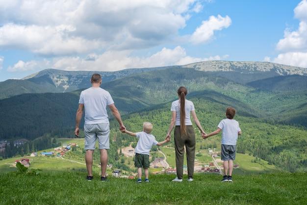 Feriado familiar. pais e dois filhos admiram a vista do vale. montanhas à distância. vista traseira
