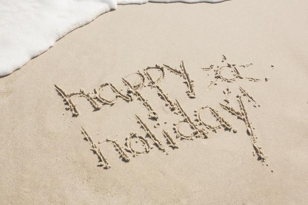 Feriado feliz escrito na areia