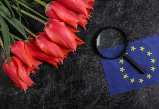 Feriado internacional europeu. dia do conhecimento, dia do professor. buquê de tulipas, bandeira da união europeia em um fundo de quadro de giz.