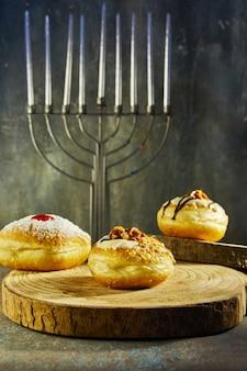 Feriado judaico de hanukkah à superfície com menorá e donuts