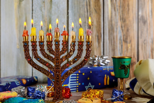 Feriado judaico hanukkah com candelabros tradicionais de menorá e piões de madeira girando