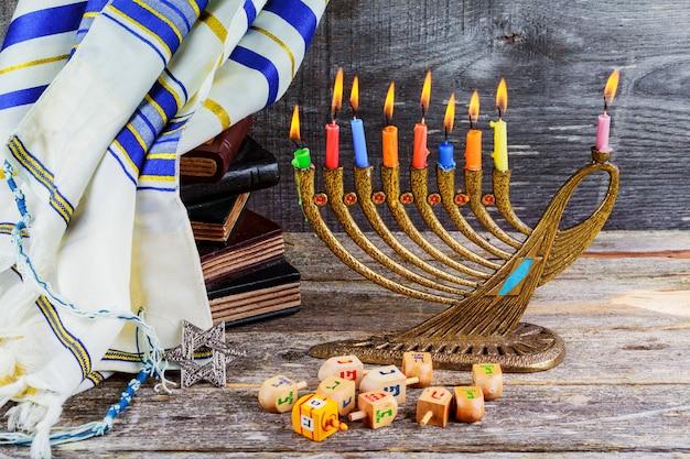 Feriado judaico hanukkah com menor candelabro tradicional e dreidels de madeira girando