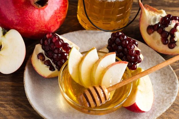 Feriado judaico rosh hashaná ou conceito de dia de festa de maçã, com maçãs vermelhas e mel na jarra, sobre fundo de madeira.