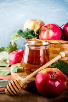 Feriado judaico rosh hashaná ou conceito de dia de festa de maçã, com maçãs vermelhas, folhas de maçã e mel no pote