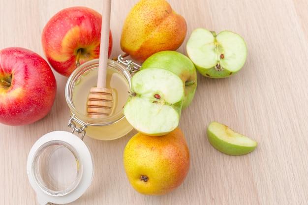 Feriado judaico rosh hashanah com mel e maçãs na mesa de madeira.